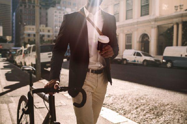 自転車を押しながらコーヒーを持って歩く男性