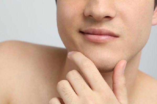 顎を触る男性