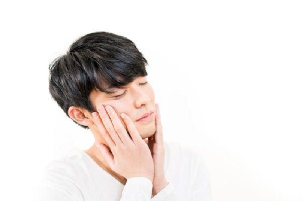 頬を触る日本人男性